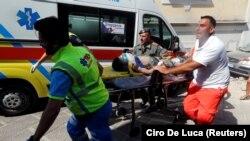 Спасувачките екипи со повредено дете од земјотресот во Италија.