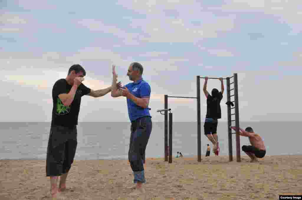 Потренироваться приходят не только молодые мужчины, пенсионеры тоже поддерживают себя в форме на песчаном берегу