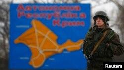 Російський військовий на чергуванні поблизу мапи Криму під час окупації півострова, березень 2014 року