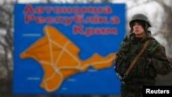 Российский солдат стоит перед картой Крыма. Керчь, 4 марта 2014 года.