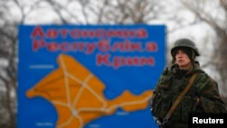 Ukraine -- A Russian serviceman stands on duty near a map of the Crimea region near the city of Kerch, March 4, 2014
