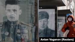 A woman walks past billboards with portraits of Red Army soldiers during the celebrations of Victory Day, which marks the anniversary of the victory over Nazi Germany in World War II, in St. Petersburg, Russia, on May 9.