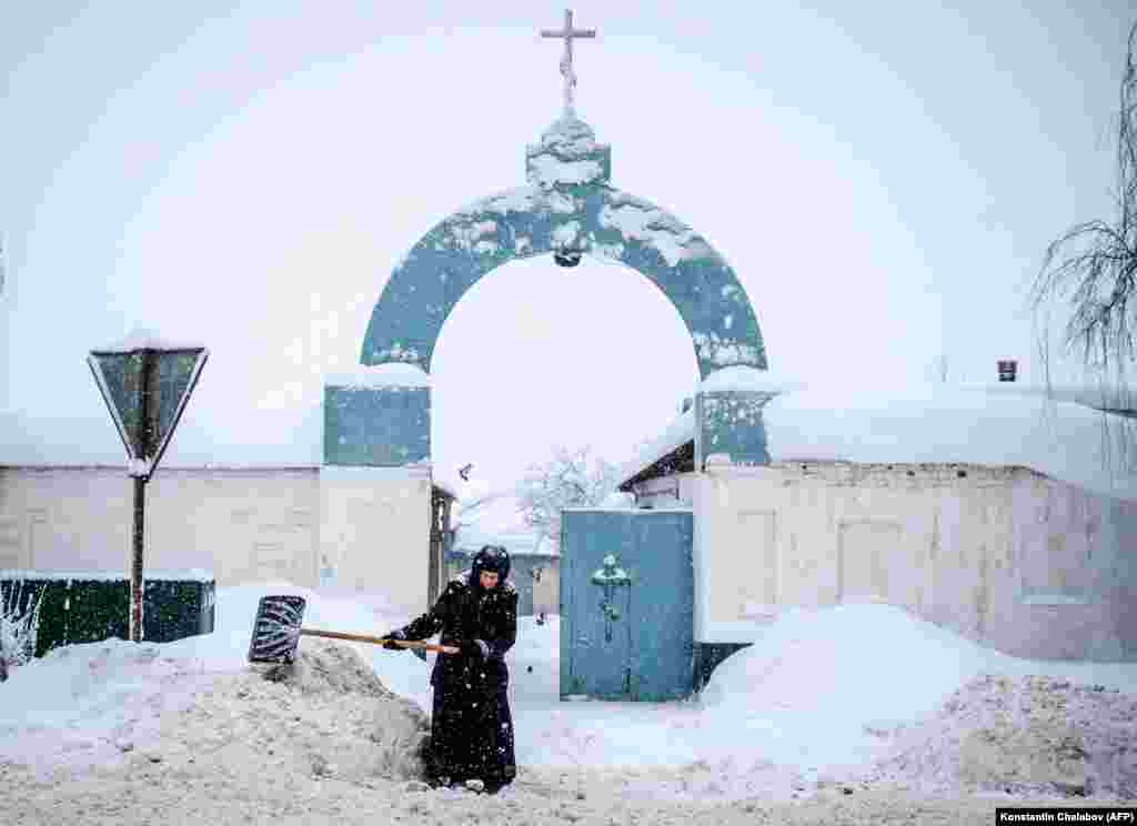 A nun shovels snowl in front of the gate of the Bogoslovsky nunnery in the village of Bogoslovo in the Vladimir region, some 190 kilometers outside Moscow, on February 4. (AFP/Konstantin Chalabov)
