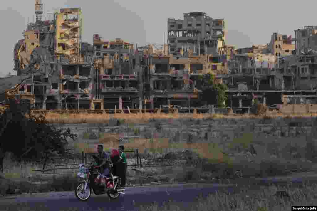 People ride a motorcycle past damaged buildings in the old town of Homs, Syria. (AP/Sergei Grits)