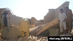 FILE: Residents inspect the ruins of a house destroyed in fighting in Kunduz's Dasht-e-Archi district.