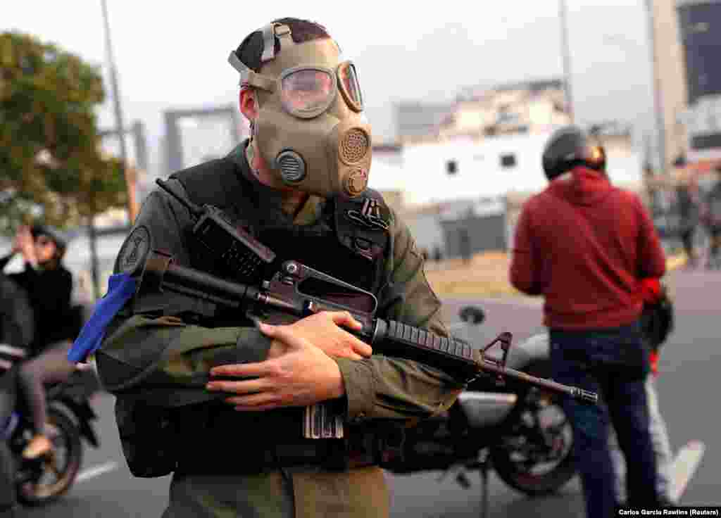 "An armed man with a gas mask. According to Reuters, protests are planned for May 1, including what Guaido has said will be ""the largest march in Venezuela's history,"" part of what he calls the ""definitive phase"" of his effort to take office in order to call fresh elections."