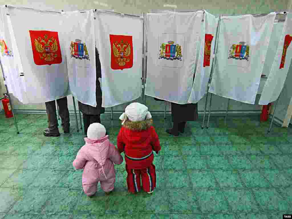 Children wait as their parents vote at a polling station in Ivanovo, Russia. - The vast majority of the mandates in the local legislative election on March 14 went to the ruling United Russia party, but support for the party in percentage terms declined. Photo by ITAR-TASS