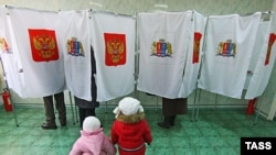 Children wait as their parents vote in ballot booths at a polling station in Ivanovo.