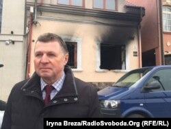 Йосип Борто на тлі будівлі після підпалу