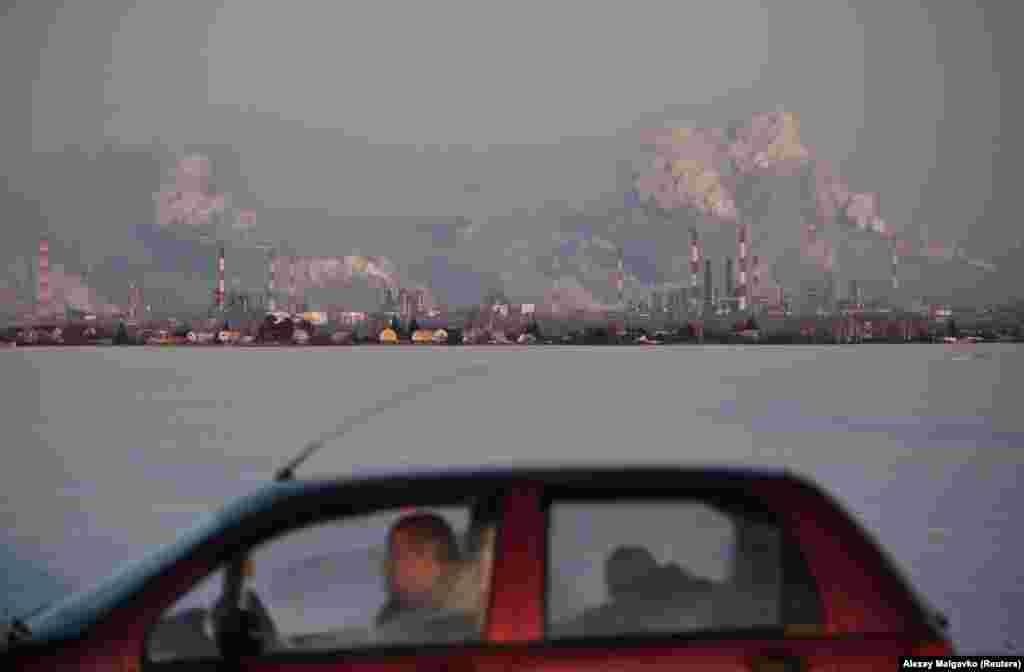 A car drives past the Gazprom Neft oil refinery in Omsk, Russia. (Reuters/Alexey Malgavko)