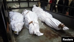 The bodies of what activists say are victims of shelling by the Syrian Army are seen in the Sunni district of Bab Amro in Homs on February 8.