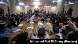 گروهی از مسحیان مصر در حال سوگواری بر تابوت کشتهشدگان حمله روز جمعه در کلیسایی در مینیا