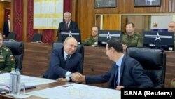 Фото державного сирійського агентства SANA: Путін і Асад тиснуть одне одному руки в командному пункті російських військ у Сирії, 7 січня 2020 року