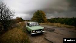 Заброшенная машина на дороге в поселке Дружба, расположенном вблизи складов боеприпасов