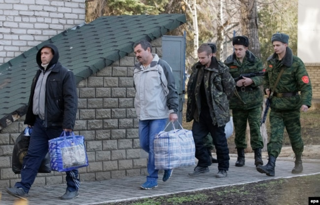 Ukrainian war prisoners are guarded by Luhansk separatists during a prisoner exchange in February 2016.