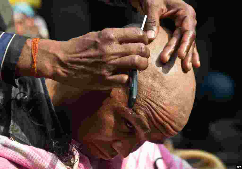 An Indian demonstrator gets his head shaved in protest following the death of a gang-rape victim in New Delhi. The brutal gang-rape of the 23-year-old medical student on December 16 has led to a bout of national soul-searching over the treatment of women in Indian society and provoked daily protests. (AFP/Prakash Singh)