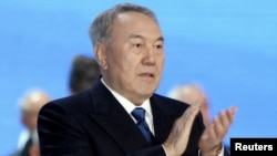 Kazakh President and presidential candidate Nursultan Nazarbaev applauds as he attends a session of the Assembly of People of Kazakhstan in Astana on April 23.