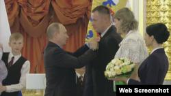 Владимир Путин вручает награду семье Новиков