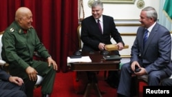 Venezuela's then-President Hugo Chavez (left) and Belarusian envoy Viktar Sheiman (right) talk during a meeting in Caracas in October 2011.