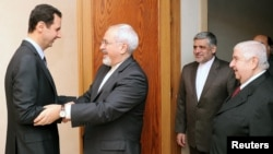 Syrian President Bashar al-Assad (left) welcomes Iranian Foreign Minister Mohammad Javad Zarif before a meeting in Damascus on January 15.