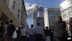 أميركيون في مانهاتن يراقبون بصدمة آثار إصطدام طائرتين ببرجي مركز التجارة العالمي بنيويورك في 11 أيلول 2001
