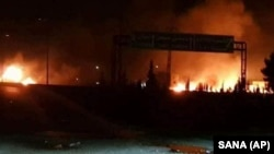 This photo released on Wednesday, May 9, 2018, by the Syrian official news agency SANA, shows flames rising after an attack in an area known to have numerous Syrian army military bases, in Kiswa, south of Damascus, Syria.