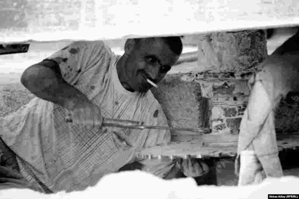 Zakir adjusts one of the stone-cutting machines, which require frequent servicing.