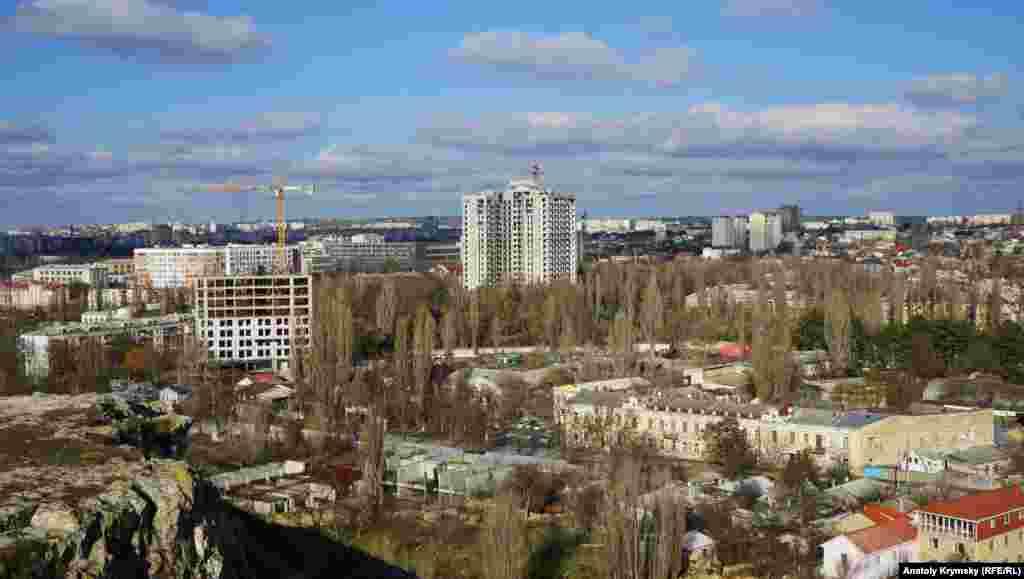 З Петровських скель добре видно, як ударними темпами забудовується одна з колишніх зелених зон міста – сквер навколо знесеного кінотеатру «Мир». У центрі кадру – 19-поверховий «люксовий» клубний будинок «Тріумф» будівельної фірми «Владоград»