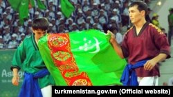 Turkmen wrestlers carry the national flag at the opening ceremony of the Asian Indoor and Martial Arts Games in Ashgabat on September 17.