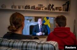 Сям'я глядзіць выступ прэм'ер-міністра Швэцыі з нагоды каранавіруснага крызісу
