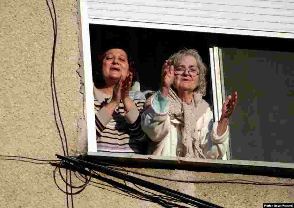 Albanians confined to their home clap along to a singer entertaining from a communal courtyard in Durres on April 7.