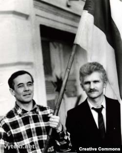 Валеры Буйвал і Алесь Бяляцкі з нацыянальным сьцягам ля сядзібы БНФ