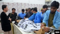 Paramedics, colleagues and other men stand beside the bodies of two policemen who were killed in Quetta on January 28.
