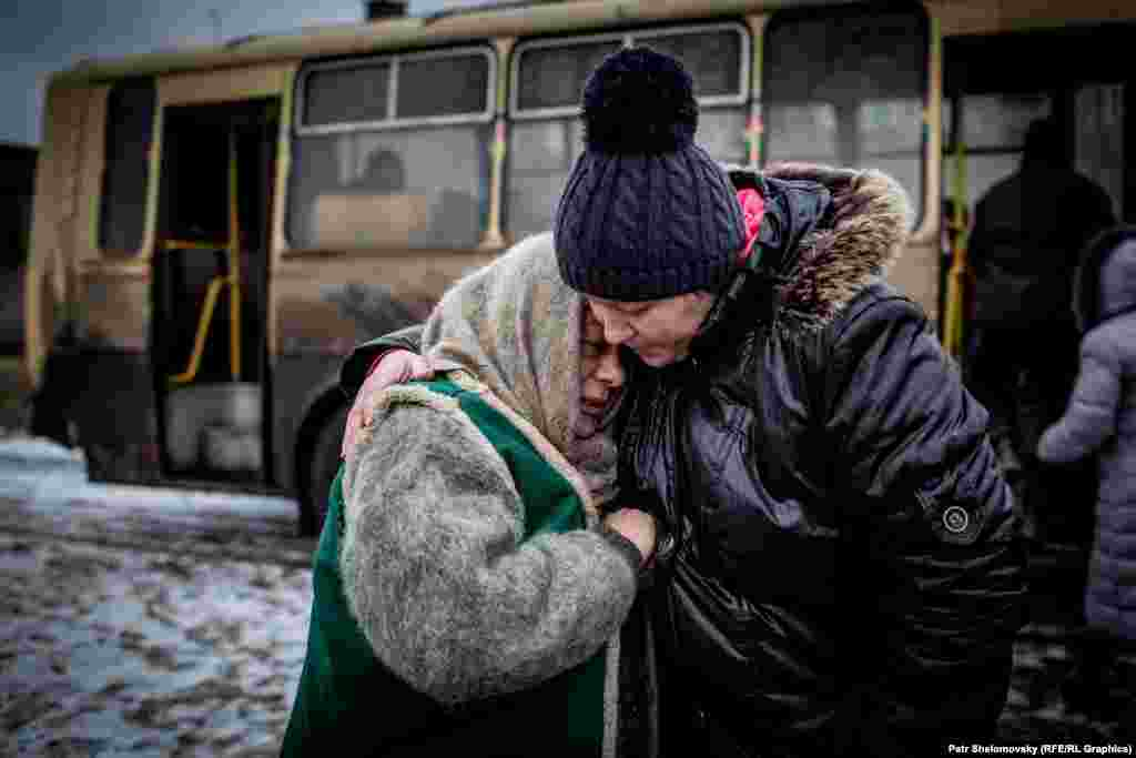 Women prepare to board a bus to leave the town on February 4.