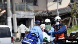 Спасатели транспортируют человека, получившего ранения в результате землетрясения. Город Машики, 15 апреля 2016 года.