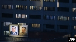 Portraits of late North Korean leaders Kim Il Sung (left) and Kim Jong Il are displayed on the side of a building in Pyongyang.