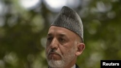 Afghan President Hamid Karzai at a July 12 news conference with his French counterpart, Nicolas Sarkozy, after Karzai's brother was shot dead earlier the same day in Kandahar