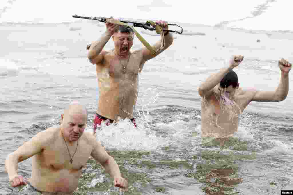Ukrainian army veterans take a dip in the freezing waters of the Dnieper River during Orthodox Epiphany celebrations in Kyiv on January 19. (REUTERS/Vladimir Sindeyev).