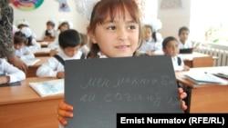 """Девочка держит надпись: """"Я соскучилась по школе"""". Ош, 17 ноября 2011 года. Иллюстративное фото."""