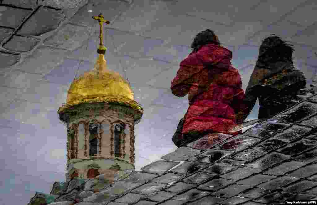 Two women are reflected in a puddle as they walk across Red Square in Moscow on April 26. (AFP/Yuri Kadobnov)