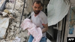 A Syrian man carries the body of an infant retrieved from under the rubble of a building following a reported air strike on the Al-Muasalat area in the northern Syrian city of Aleppo on September 23.