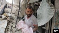 Howa zarbasyndan soň ýogalan çagany göterip barýan erkek, Aleppo, 23-nji sentýabr, 2016 ý.