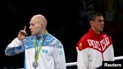 Казахстанский боксер Василий Левит (слева) жестом призывает не шуметь болельщиков на трибунах, возмущенных судейством финального поединка Олимпиады в весовой категории до 91 килограмма (победу присудили россиянину Евгению Тищенко). Рио-де-Жанейро, 16 августа 2016 года.