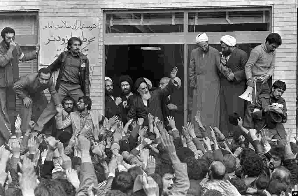 Khomeini waves to followers as he appears on the balcony of his headquarters in Tehran on February 2, 1979.