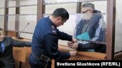 С подсудимого пастора Бахтжана Кашкумбаева снимают наручники в зале суда. Астана, 22 января 2014 года.