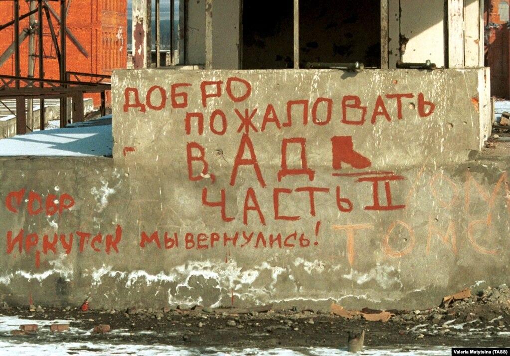 """Грозныйдың шетіндегі қираған ғимараттың бірінің қабырғасындағы """"Тозаққа қош келдіңіздер. 2-бөлім"""" деген жазу жазылған."""