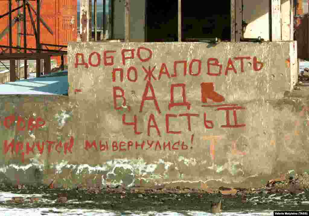"The words ""Welcome to Hell, Part II"" painted in red on a hunk of concrete on the outskirts of Grozny. The other wording refers to a unit of federal forces from the Irkutsk region, far away in eastern Siberia, and says: ""We're back."""