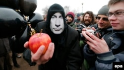 A protester wearing a mask of Russian President Vladimir Putin participates in a rally in protest against Russian actions in Crimea in St. Petersburg in March 2014.