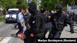 Сотрудники полиции в масках задерживают предполагаемого участника несанкционированной мирной акции протеста. Алматы, 10 мая 2018 года.