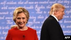 Кандидаты в президенты в США Хиллари Клинтон и Дональд Трамп покидают сцену после дебатов. Нью-Йорк, 26 сентября 2016 года.